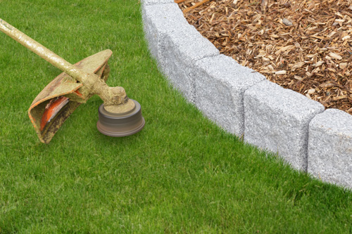 trimming grass on mulch wall